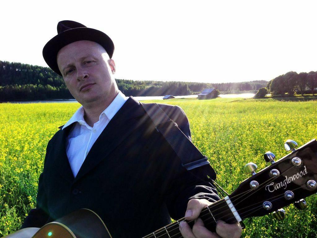 Tangokuningas Erkki Räsänen kitaroineen etualalla. Taustalla kesäinen rypsipelto, aurinko paistaa ja on KESÄ!
