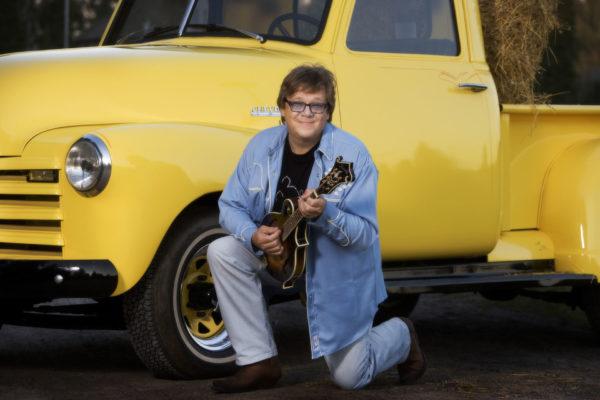 Mikko Alatalo toinen jalka polvillaan kädessä mandoliini ja taustalla keltainen amerikkalainen auto